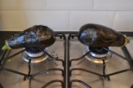 Burning aubergines over gas hob